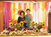Mother and daughter behind buffet table — Stock Photo