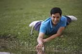Hispanic man reaching for golf ball in water — Stock Photo