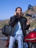 Woman on motorcycle talking on cell phone — Stock Photo