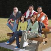 Multi-ethnic friends sitting on picnic table — Stock Photo