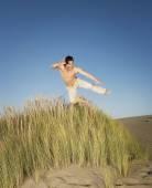 Pacific Islander man jumping on beach — Stock Photo