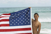 Hispanic teenaged boy holding American flag — Foto de Stock