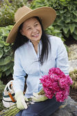 Senior Asian woman holding flowers — Stock Photo