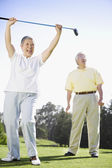 Senior Asian woman cheering on golf course — Stock Photo