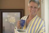 Hispanic mann hält kaffee und zeitung — Stockfoto
