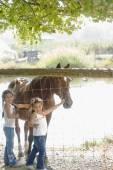 Hispanic sisters petting horse — Stock Photo