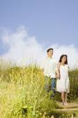 Asian couple holding hands in field — Stock Photo
