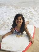 Pacific Islander girl laying on boogie board — Stock Photo