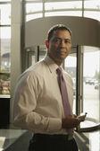 Hispanic businessman holding electronic organizer — Stock Photo
