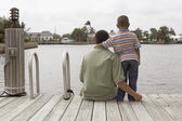 Hispanic father and son on dock — Stock Photo
