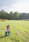 Hispanic sisters hugging in field — Stock Photo