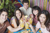 Young Hispanic friends toasting with cocktails — Stock Photo