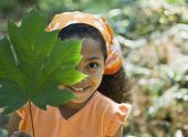 Girl holding leaf in front of face — Stock Photo