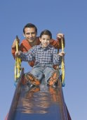 Hispanic father and son at top of slide — Stock Photo