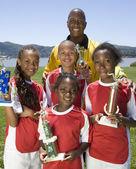 Multi-ethnic children holding soccer trophies — Stock Photo