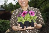 Senior Asian man holding potted plants — Stock Photo