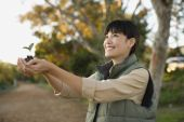 Asian woman holding small plant — Stock Photo