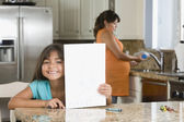 Hispanic girl holding drawing of baby — Foto de Stock