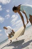 African couple laying mat on sand — Stock Photo