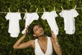 Hispanic woman hanging baby clothing on clothes line — Stock Photo