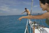 Multi-ethnic couple pointing on sailboat — Stock Photo