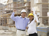 Pregnant Asian couple cheering at construction site — Stock Photo