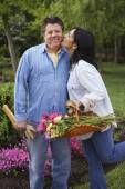 Hispanic woman kissing husband on cheek — Stockfoto