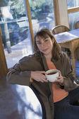 Hispanic woman holding coffee mug — Stock Photo