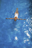 Senior woman floating in swimming pool — Stock Photo
