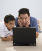 Asian father and son looking at laptop — Φωτογραφία Αρχείου