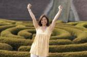 Asian woman with arms raised — Stock Photo