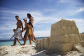 Hispanic family walking past sandcastle — Stock Photo