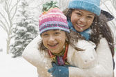 Multi-ethnic girls hugging in snow — Stock Photo