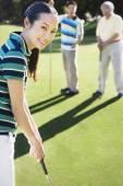 Asian woman playing golf — Stock Photo