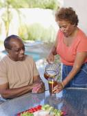 Woman pouring iced tea for husband — Stock Photo