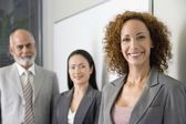 Multi-ethnic businesspeople next to wall — Stock Photo