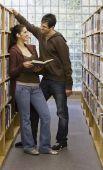 Multi-ethnic couple in library — Stock Photo