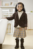 African girl standing next to arm chair — Stock Photo
