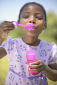 African girl blowing bubbles — Stock Photo