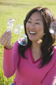 Asian woman blowing bubbles — Stockfoto