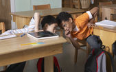 Multi-ethnic boys whispering in class — Stock Photo