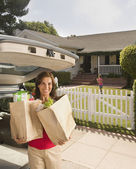 Hispanic woman holding groceries in front of house — Stock Photo