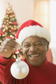 African man wearing Santa hat and holding Christmas ornament — Stock Photo