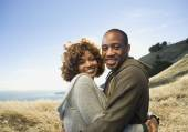 African American couple hugging in field — Stock Photo