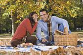Hispanic couple telling secret at picnic — Stock Photo