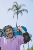 Hispanic man holding skateboard — Stock Photo