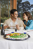 Multi-ethnic couple eating sush — Stock Photo