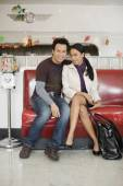 Asian couple sitting on sofa — Stockfoto