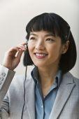 Asian businesswoman wearing headset — Stock Photo