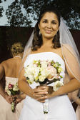 Hispanic bride holding bouquet — Stock Photo